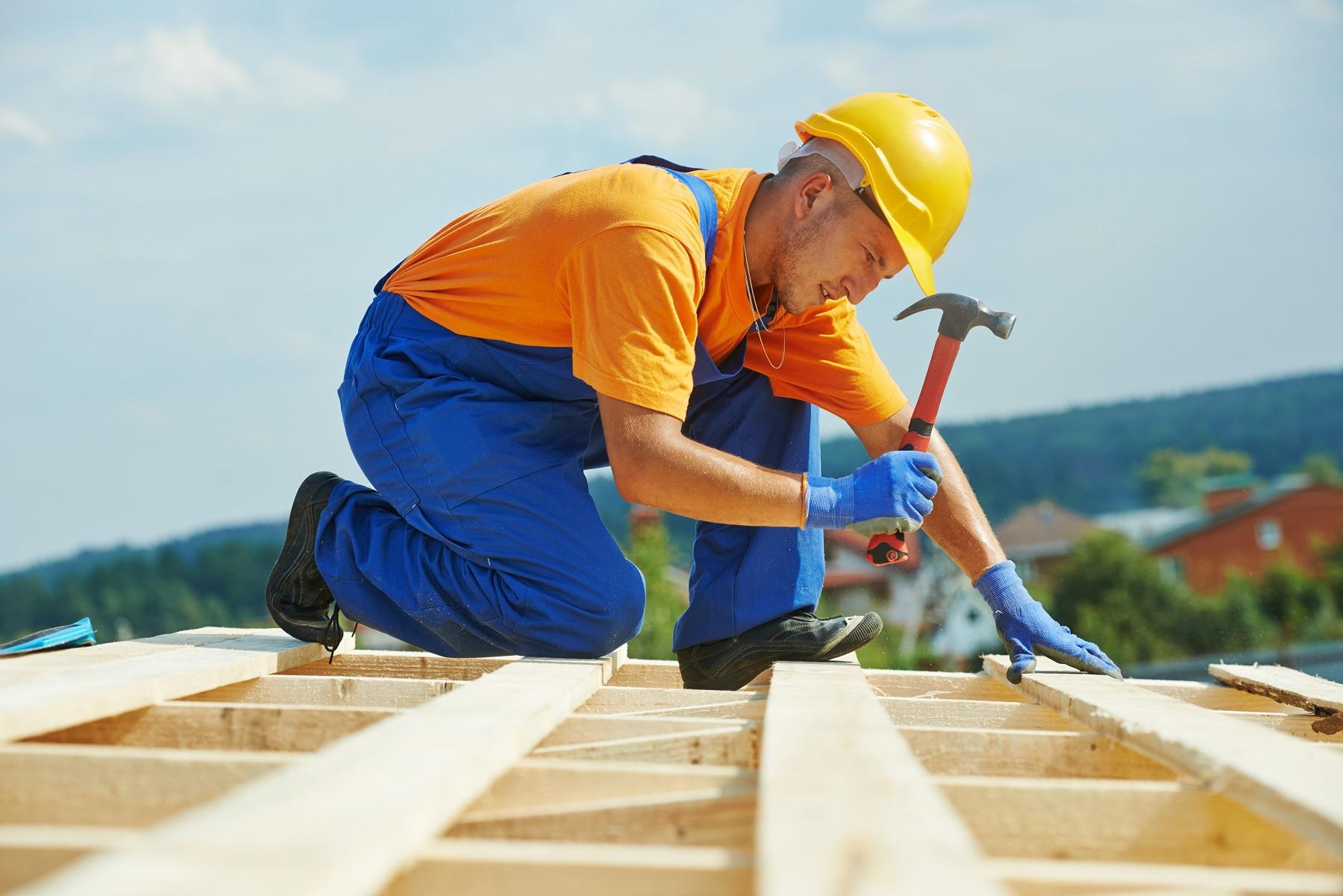 Construction couvreur ouvrier charpentier clouer planche de bois avec un marteau sur les travaux d'installation sur le toit