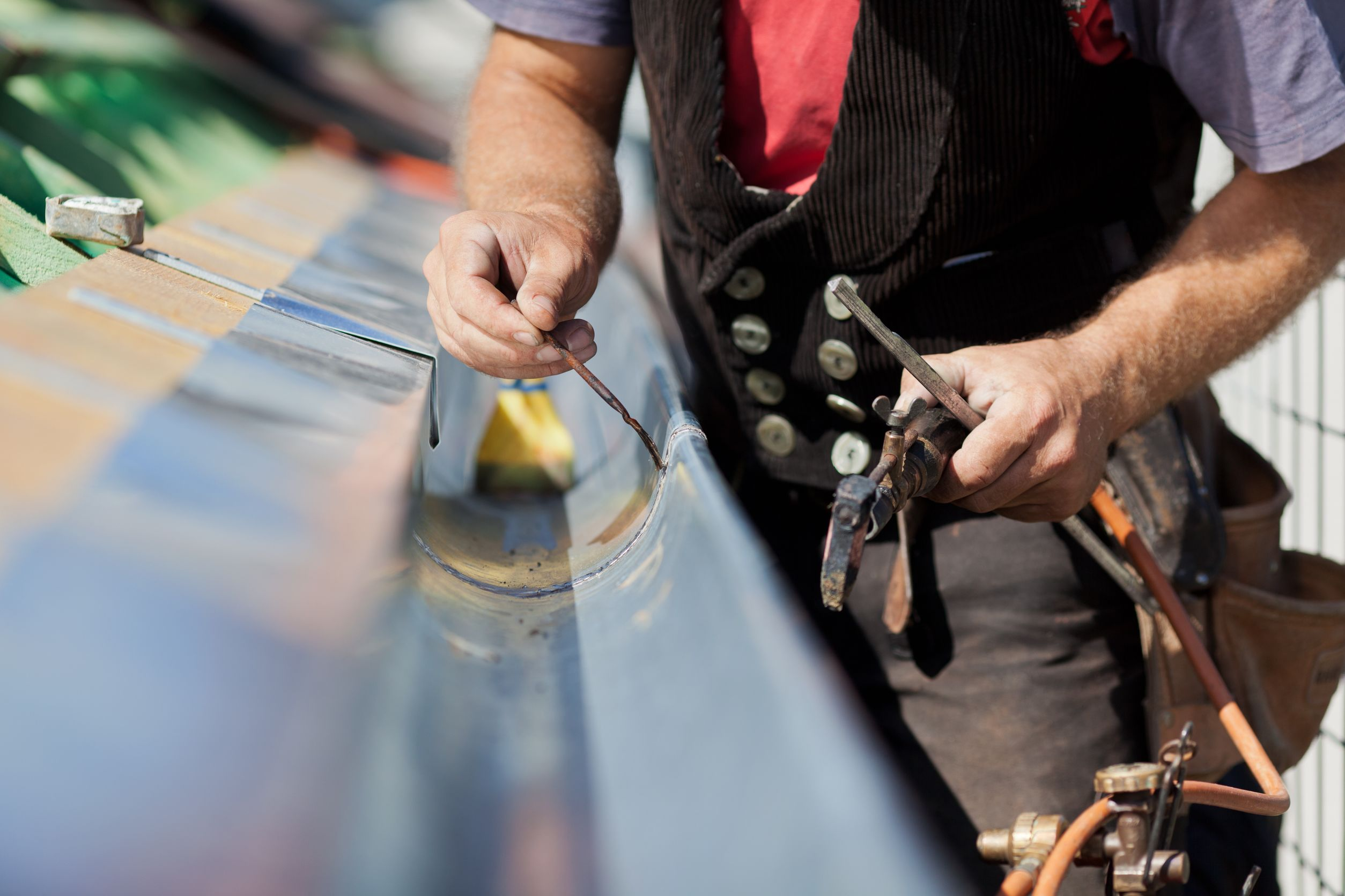 21260944 – close-up of a roofer welding the gutter on a new roof
